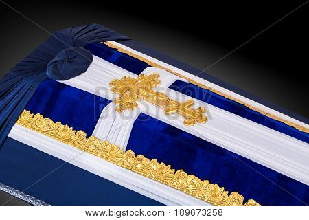 closed coffin covered with blue and white cloth decorated with Church gold cross isolated on gray luxury background. Ritual objects for burial. Surrender body dust of the earth. Close-up details.