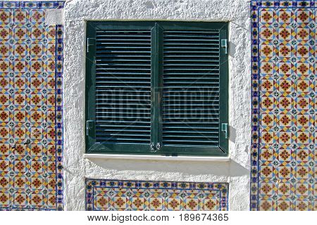 A window with it's shutters closed on the side of a traditional house in Lisboa.