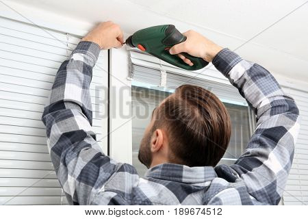 Man installing window shades at home