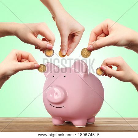 Hands putting coins into piggy bank on color background. Money savings concept