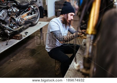 Side view portrait of brutal tattooed man repairing and customizing motorcycles
