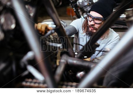 Portrait of tattooed man working in garage customizing  motorcycle and tuning it up
