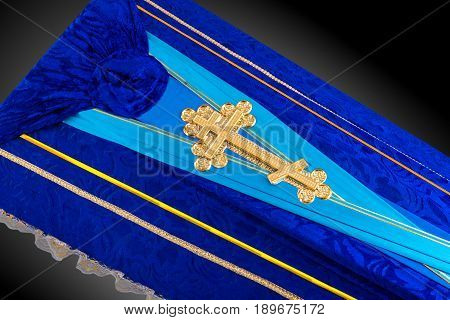 closed blue coffin covered with cloth isolated on gray background. coffin close-up with gold Church cross on royal background. Ritual objects for burial. Surrender body dust of the earth. Christian funeral ritual