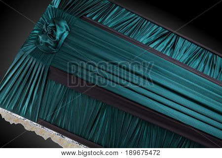 closed dark green coffin covered with elegant cloth isolated on gray background. coffin close-up on royal background. Ritual objects for burial. Surrender body dust of the earth. Christian funeral ritual