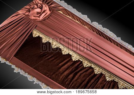 closed brown coffin covered with elegant cloth isolated on gray background. coffin close-up with gold flowers on royal background. Ritual objects for burial. Surrender body dust of the earth. Christian funeral ritual