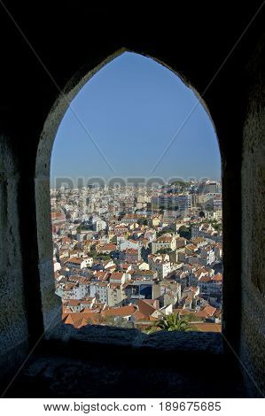 A down angle of the city Lisboa in Portugal viewed through an old window.