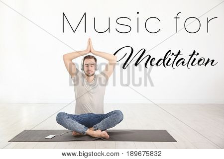 Young man listening to music during yoga practice at home. Concept of melody for meditation