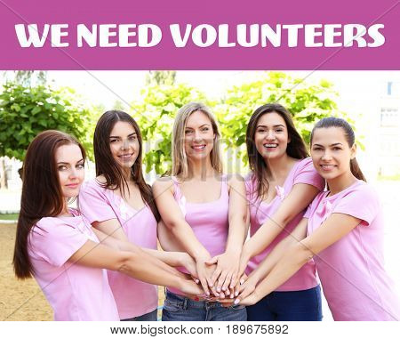 Yong women with pink ribbons on shirts putting hands together. Text WE NEED VOLUNTEERS on background. Breast cancer concept