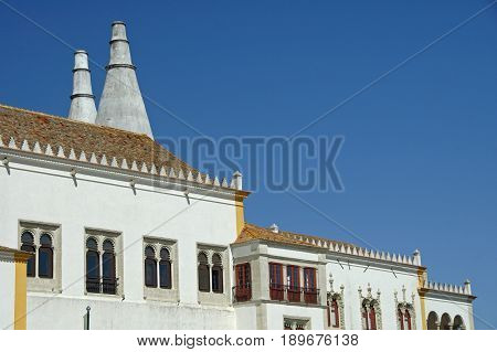 A massive white bulding at the heart of Sintra with two enormous chimneys sticking out of it.