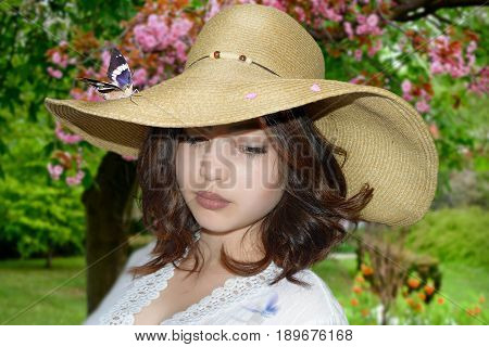 photography with scene of the beautiful young girl with butterfly in straw hat on background of the flowering garden