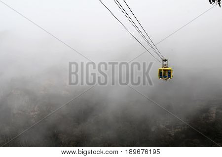 KATOOMBA AUSTRALIA - SEPTEMBER 25 2015: The Scenic World Skyway comes out of the mist that swirls around the Blue Mountains a World Heritage site in New South Wales Australia on a rainy spring day.