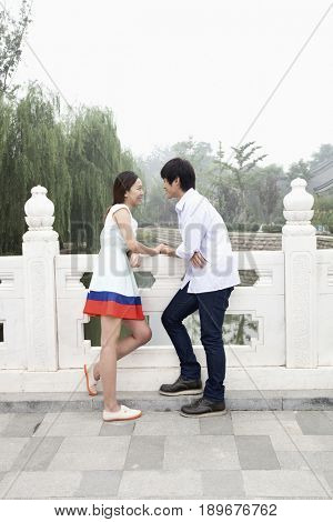 Chinese couple standing by carved railing