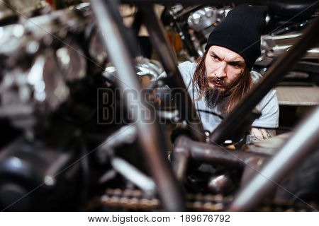 Portrait of focused tattooed man working in garage tuning up motorcycle