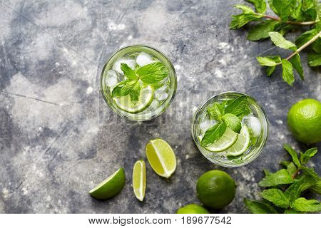 Mojito cocktail alcohol refreshment drink in highball glass, summer tropical vacation beverage with rum, mint leaves, lime citrus juice, soda water and ice on concrete table. Top view