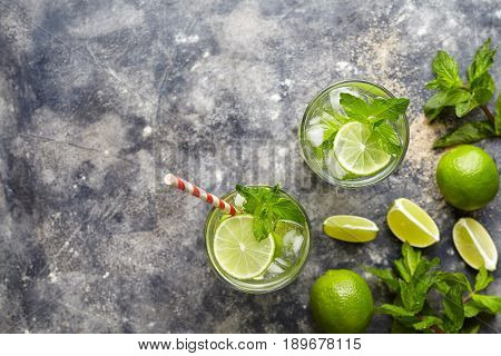 Mojito cocktail alcohol bar drink traditional fresh tropical beverage top view copy space two highball glass, with rum, citrus slice, spearmint, lime juice, soda water and ice on concrete table.