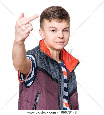 Emotional portrait of irritated teen boy - isolated on white background. Furious teenager looking with anger at camera and show middle finger or fuck you sign.