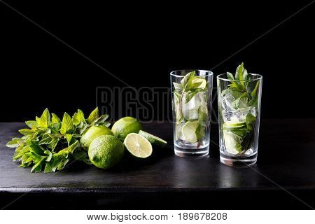 Mojito traditional refreshing cocktail alcohol drink in glass bar preparation with lime, mint leaves, sugar, and rum. Dark black background with copy space for text
