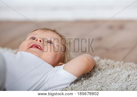 Cute baby boy laying on carpet floor andd loking up