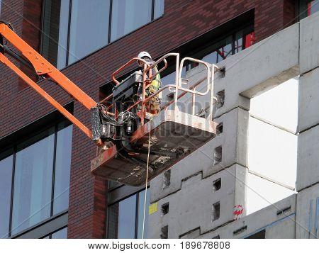 worker on an elevated construction platform on modern building development poster