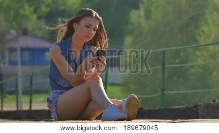 The girl is holding smartphone. Internet girl outdoor in smartphone social media sits on iron bridge