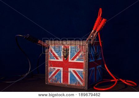 Concept of terrorism.England flag box and jumper cables on dark background