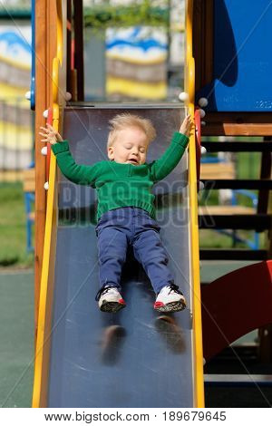 Portrait of toddler child outdoors. One year old baby boy wearing green sweater at playground slide
