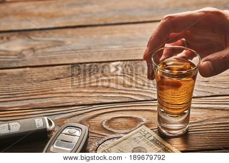 Man's hand reaching to glass of tequila or alcohol drink and car key on rustic wooden table. Drink and drive and alcoholism concept. Safe and responsible driving concept.