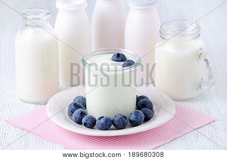 a cup of yogurt with blueberrys and different bottles of drink yogurt and milk on a plate, napkin on the table