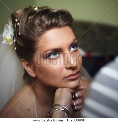 Bride with deep blue eyes looks up while woman checks her make up