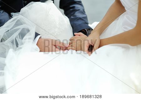 Groom tenderly touching bride hand during wedding ceremony