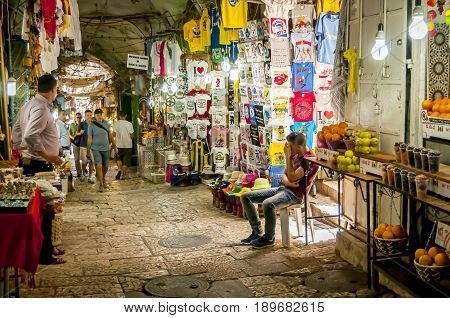 JERUSALEM, ISRAEL. May 14, 2016. The busy Kind David street of the Souk El Bazaar tourist market in the Old city Jerusalem with tourists passing by and a local Arab merchant in the souvenir shop.