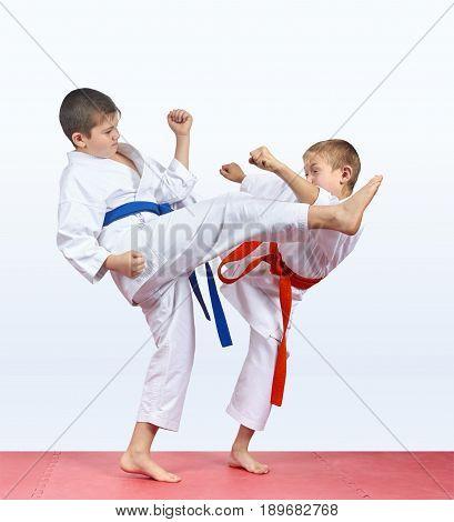 Two karateka children are beating kick leg