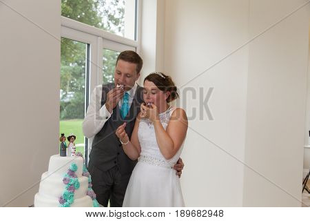 Bride And Groom Sampling Their Wedding Cake