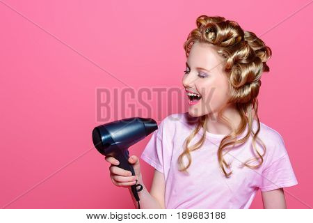 Portrait of a pretty girl teenager with curlers in her blonde hair holding hair dryer. Teen style, fashionable teen girl. Studio shot over pink background.