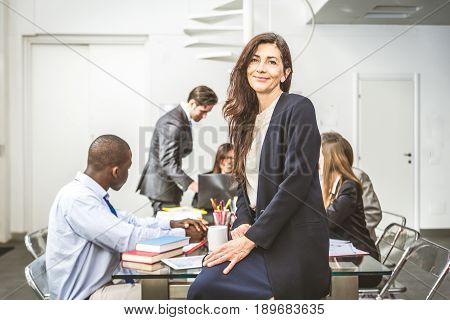 Business woman portrait - Team of businessmen in a conference meeting confident senior woman smiling at camera