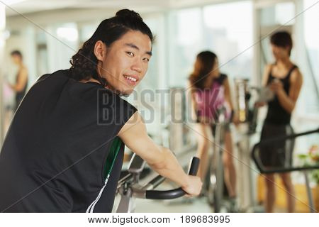Chinese man riding stationary bicycle in gym
