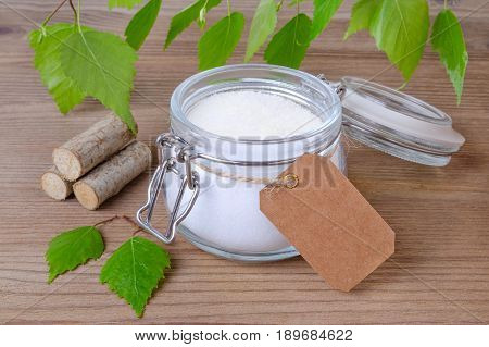 sugar substitute xylitol a glass jar with birch sugar and a label for text in your language on wooden background