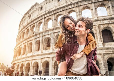 Young couple at the Colosseum Rome - Happy tourists visiting italian famous landmarks