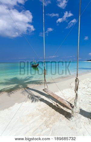 landscape with a seesaw on the sandy beach and turquoise sea. The sand falls the shadow of a palm tree.