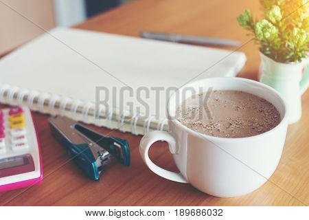Hot cups of coffee to deal with notebooks pens calculators Stapler And vases on the wood table