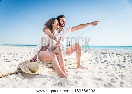 Couple strolling at the beach and smiling - Young adults enjoying summer holidays on a tropical island