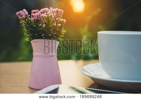 Template. The mobile , a vase of flowers and a cup of coffee
