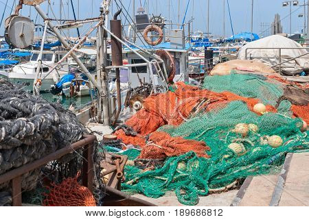 JAFFA - ISRAEL, April 10, 2017: Old Jaffa Port Tel Aviv Israel is now used as a fishing harbour and tourist attraction. Fishnet in front of Ships anchoring at the Jaffa port in a sunny day, Israel
