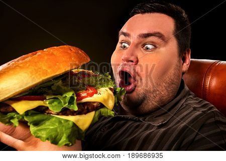 Diet failure of fat man eat fast food . Breakfast for mad overweight person who eating huge hamburger. Junk meal leads to obesity concept on black background.