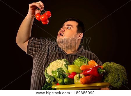 Diet fat man eating healthy food. Health breakfast with vegetables tomatoes for overweight person. Male trying to lose weight and rejoices in healthy eating. Fat man enjoying cherry tomatoes on branch