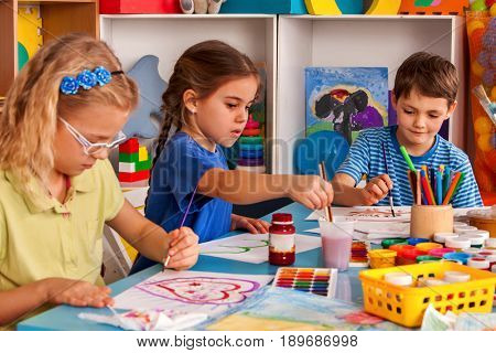 Small students painting in art school class. Child drawing by paints on table. Boy and girls in kindergarten. Drawing education develops creative abilities of children. The best children's club.