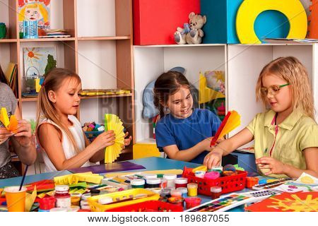 School children with scissors in kids hands cutting paper with teacher in class room. Development and social lerning. Children's project in kindergarten. Large group girls and boys together