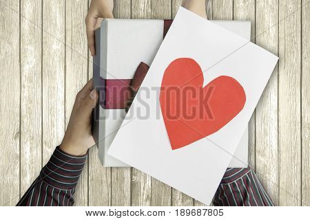 Close up of little child giving gift box and love card to her father with the wooden background