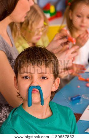 Child dough play in school. Plasticine for children. Mold from plasticine in kindergarten. Kids knead modeling clay with hands in preschool. Boy fun and makes faces in kindergarten.