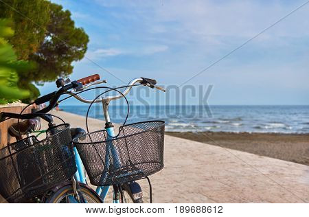 Two bicycles with baskets parked on the stone promenade near the trees and beach, with blue sea and sky in the background.